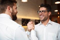 Portret van twee opgewekte gelukkige zakenlieden die handen schudden Stock Afbeeldingen