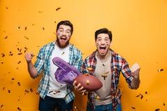 Portret van twee opgewekte jonge mensen die rugbybal houden royalty-vrije stock afbeelding