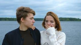 Portret van twee tieners, een kerel en een meisje, tegen de achtergrond van een rivier en een bos stock video
