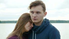 Portret van twee tieners, een kerel en een meisje, tegen de achtergrond van een rivier en een bos stock videobeelden