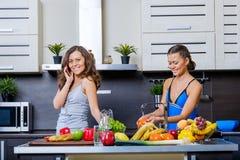 Portret van Twee tweelingzusters die pret in de ochtend hebben die ontbijt voorbereiden Stock Foto's