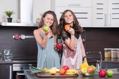 Portret van Twee tweelingzusters die pret in de ochtend hebben die ontbijt voorbereiden Stock Foto