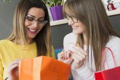 Portret van twee volwassen meisjes aangezien zij in een het winkelen zak kijken stock afbeelding