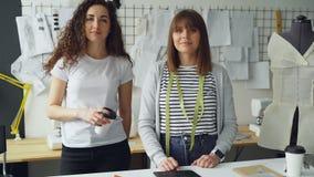 Portret van twee vrouwelijke ondernemers die van kledingsontwerpers in workshop verenigen zich en camera bekijken Één vrouw stock videobeelden