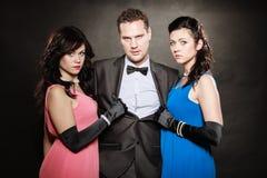 Portret van twee vrouwen en mannen één die elegante kleren op zwarte dragen Twee vrouwen en één man betrayal Royalty-vrije Stock Foto