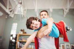 Portret van vader dragende zoon die superherokostuum dragen Stock Foto