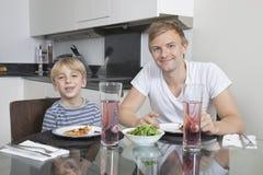 Portret van vader en zoon die bij ontbijtlijst glimlachen Stock Foto