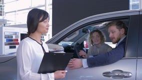 Portret van verkoopster met de cliënt van het familiepaar dat sleutels binnen auto terwijl aankoopauto op verkoopcentrum toont stock video