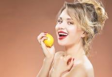 Portret van Verleidelijke Sexy Kaukasische Blonde Meisje het Bijten Citroen Stock Foto