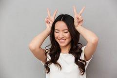Portret van vermakelijke Aziatische meisjesjaren '20 in toevallige t-shirt die pret hebben Royalty-vrije Stock Foto