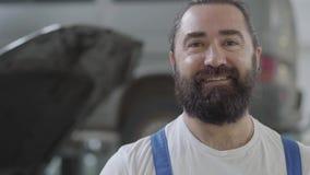 Portret van vermoeid maar het glimlachen het mooie en succesvolle gebaarde mechanische stellen in het werkhandschoenen en een moe stock footage