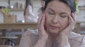 Portret van vermoeide droevige hogere vrouw die met het gekleurde zwarte hoofd van de haarholding met handen op de leerbank zitte stock video
