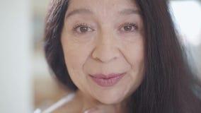 Portret van verraste hogere vrouw die met schitterend lang donker haar en prettige brede glimlach in camera binnen dicht kijken stock video