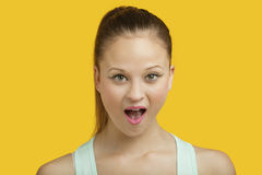 Portret van verraste jonge vrouw met mond open over gele achtergrond Stock Foto