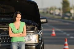 Portret van verstoorde jonge vrouw status dichtbij haar gebroken auto stock fotografie