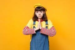 Portret van verstoorde meisjestiener in Franse baret, de handen van de denim sundress holding samen, bidden geïsoleerd op geel stock foto