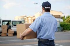 Portret van vertrouwens uitdrukkelijke koerier naast zijn leveringsbestelwagen stock afbeeldingen