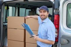 Portret van vertrouwens uitdrukkelijke koerier naast zijn leveringsbestelwagen stock fotografie