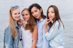 Portret van vier jonge vrouwelijke vrienden die op de overzeese kust lopen die camera het lachen bekijken stock afbeeldingen