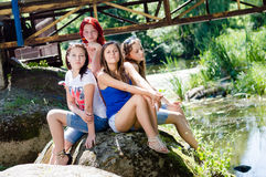 Portret van vier jonge vrouwen die van meisjesvrienden pretzitting op steen hebben die & camera op de zomer in openlucht stellen  Stock Foto's