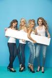 Portret van vier meisjes die een raad houden stock foto