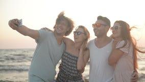 Portret van Vier Mensen met Witte Toothy Glimlachen die Selfie nemen tegen Mobiele Telefoon het Besteden Tijd samen op de Kust stock videobeelden