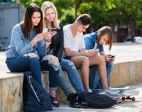 Portret van vier tieners die met hun mobiele telefoons zitten outd royalty-vrije stock afbeeldingen