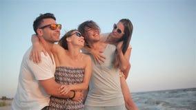 Portret van Vier Vrienden die Pret samen op de Kust hebben tijdens Windy Weather en van de Zonsondergang genieten stock footage