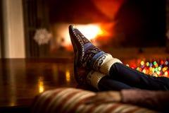 Portret van voeten bij wollen sokken die bij open haard in de winter verwarmen royalty-vrije stock fotografie