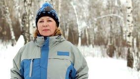 Portret van volwassen vrouw in de winterpark. stock video