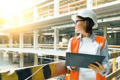Portret van volwassen vrouwelijke bouwer, ingenieur, architect, inspecteur, manager bij bouwwerf Vrouw met plan, digitale tablet stock foto