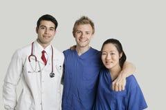Portret van vriendschappelijk medisch team die zich over grijze achtergrond bevinden Stock Afbeeldingen