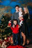 Portret van vriendschappelijke familie die camera op Kerstmisavond bekijken Stock Foto's