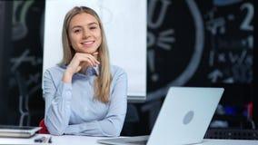 Portret van vriendschappelijke glimlachende jonge onderneemster die camera bekijken die goede tijd op modern kantoor hebben stock videobeelden