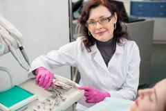 Portret van vriendschappelijke vrouwelijke tandarts met vrouwelijke patiënt in het tandbureau tandheelkunde Tand apparatuur stock afbeeldingen