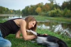 Portret van vrij aantrekkelijke meisje het besteden tijd met haar witte en zwarte hond in openlucht tijdens de zomerdag op rivier Stock Foto's