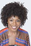 Portret van vrij Afrikaanse Amerikaanse vrouw die in traditionele slijtage over grijze achtergrond glimlachen royalty-vrije stock afbeeldingen