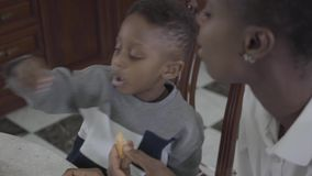Portret van vrij Afrikaanse Amerikaanse vrouwenzitting met haar weinig zoon door lijst samen met koekjes te spelen Familie stock videobeelden