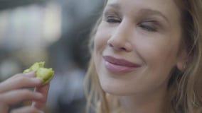 Portret van vrij blonde vrouw die met krullend haar groene makaron in het restaurant dicht omhoog eten De dame die haar sluit stock footage