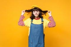 Portret van vrij heldere meisjestiener in Frans die baret en denim sundress holdingshaar op gele muur wordt geïsoleerd royalty-vrije stock afbeelding