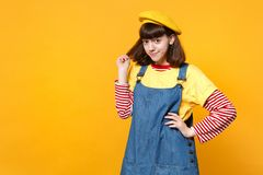Portret van vrij heldere meisjestiener in Frans die baret en denim sundress holdingshaar op gele muur wordt geïsoleerd stock fotografie