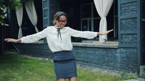 Portret van vrij het Afrikaanse Amerikaanse meisje dansen die in openlucht alleen pret hebben stock footage