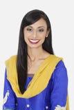 Portret van vrij Indische vrouw die in traditionele slijtage tegen grijze achtergrond glimlachen Royalty-vrije Stock Afbeeldingen