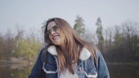 Portret van vrij jong glamourbrunette in modieus glazen en jeansjasje die in de camera kijken Mooi stock video