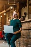 Portret van vrij jonge bedrijfsvrouw die in glazen op werkplaats zitten royalty-vrije stock foto