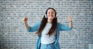 Portret van vrij jonge dame in hoofdtelefoons die genietend van muziek dansen stock footage