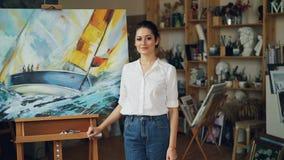 Portret van vrij jonge dameschilder die camera en het glimlachen binnen status dichtbij haar mooi beeld op schildersezel bekijken stock video