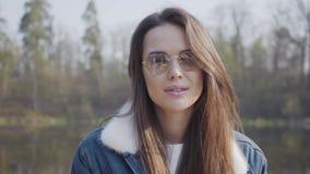 Portret van vrij jonge glamour glimlachende vrouw die in modieus glazen en jeansjasje in de camera kijken De dame stock footage