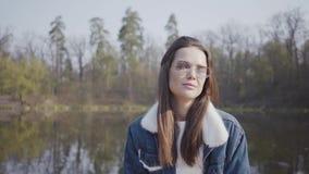 Portret van vrij jonge glamour glimlachende vrouw die in modieus glazen en jeansjasje in de camera kijken Mooi stock video