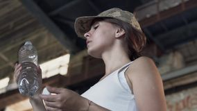 Portret van vrij jonge vrouw in het militaire drinkwater van GLB van de fles in de stoffige vuile verlaten bouw E stock footage